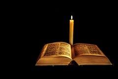 Sagrada Biblia con la vela foto de archivo