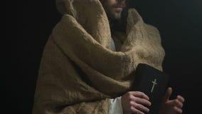 Sagrada Biblia de la demostración de Jesus Christ a la cámara, canones de dios, símbolo religioso de la vida almacen de metraje de vídeo