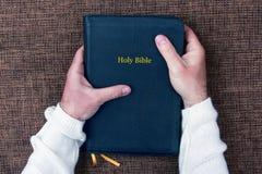Sagrada Biblia en las manos del hombre Fotografía de archivo