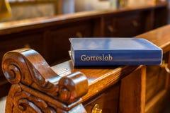 Sagrada Biblia que miente en un banco en iglesia Imagen de archivo