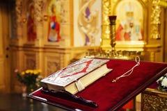 Sagrada Biblia y cruz ortodoxa en iglesia ortodoxa Fotos de archivo