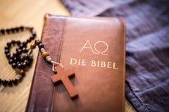 Sagrada Biblia y rosario: Biblia y rosario cristianos en un escritorio de madera foto de archivo libre de regalías