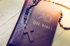Sagrada Biblia y rosario: Biblia y rosario cristianos en un escritorio de madera imagen de archivo