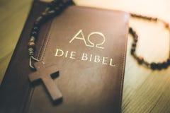 Sagrada Biblia y rosario: Biblia y rosario cristianos en un escritorio de madera fotos de archivo