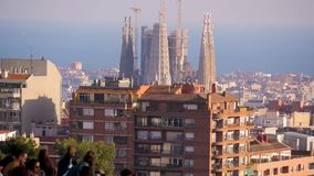 The Sagrada de Familia from afar with a crowd of tourists in the foreground. Gaudi park stock footage