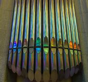 Sagrada Família`s organ. Close up of Sagrada Família`s organ with multicolored reflections of stained glass windows in its pipes. The instrument has 26 stock image