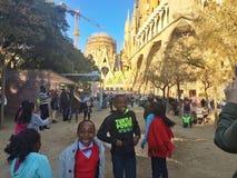 SAGRADA FAMILIA,巴塞罗那, 2015年12月-黑人孩子获得与街道艺术家做的肥皂泡的乐趣 库存照片