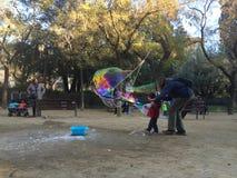 SAGRADA FAMILIA,巴塞罗那, 2015年12月-孩子做的肥皂泡在街道艺术家帮助下  免版税库存图片