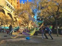 SAGRADA FAMILIA,巴塞罗那, 2015年12月-孩子获得与街道艺术家做的肥皂泡的乐趣 免版税图库摄影