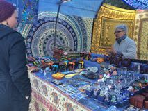 SAGRADA FAMILIA,巴塞罗那, 12月2015街道卖主销售纪念品Sagrada familia前面  免版税库存图片