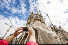 Sagrada Familia (圣洁家庭) 观光的公共汽车 拍照片的手 免版税库存照片