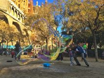 SAGRADA FAMILIA, BARCELONA, December 2015- child have fun with soap bubbles made by street artist Royalty Free Stock Photography