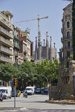 Sagrada Familia in Barcelona, Spain. Barcelona, Spain - May 25 2015: Traffic of cars and motorcycles in a street leading to the Sagrada Familia Cathedral of Stock Photography