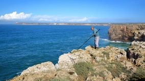 Fisherman angling above the high cliffs at Sagres Fortress Fortaleza with Cabo de Sao Vicente lighthouse in the background. SAGRES, PORTUGAL - NOVEMBER 12, 2018 stock image