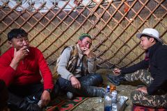 Kazakh family of hunters with golden eagles inside the mongolian Yurt. Royalty Free Stock Image