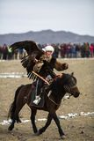 Berkutchi - Kazakh hunter with Golden eagle, while hunting to the hare in desert mountain of Western Mongolia. SAGSAY, MONGOLIA - SEP 30, 2017: Berkutchi royalty free stock photos