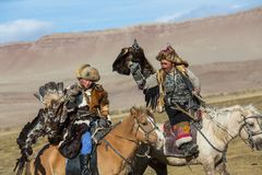 Eagle Hunter teaches her young daughter hunting with birds of prey to the hare in desert mountain of Western Mongolia. SAGSAY, MONGOLIA - SEP 28, 2017: Eagle Stock Photography