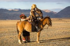 Eagle Hunter teaches her young daughter hunting with birds of prey to the hare in desert mountain of Western Mongolia. SAGSAY, MONGOLIA - SEP 28, 2017: Eagle Stock Photos