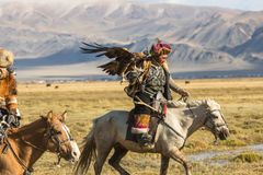 Eagle Hunter teaches her young daughter hunting with birds of prey to the hare in desert mountain of Western Mongolia. SAGSAY, MONGOLIA - SEP 28, 2017: Eagle Royalty Free Stock Images