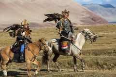 Kazakh Eagle Hunter Berkutchi with horse teaches his daughter to hunting to the hare with a golden eagles. SAGSAY, MONGOLIA - SEP 28, 2017: Eagle Hunters Royalty Free Stock Photo