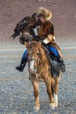 Golden Eagle Hunter teaches her young daughter hunting with birds of prey to the hare in desert mountain of Western Mongolia. SAGSAY, MONGOLIA - SEP 28, 2017 Royalty Free Stock Photo