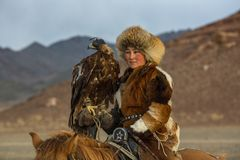 Golden Eagle Hunter teaches her young daughter hunting with birds of prey to the hare in desert mountain of Western Mongolia. SAGSAY, MONGOLIA - SEP 28, 2017 Stock Images