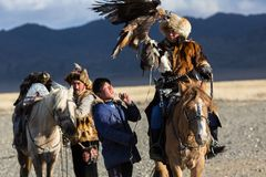 Golden Eagle Hunter teaches her young daughter hunting with birds of prey to the hare in desert mountain of Western Mongolia. SAGSAY, MONGOLIA - SEP 28, 2017 Stock Photography