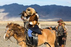 Golden Eagle Hunter teaches her young daughter hunting with birds of prey to the hare in desert mountain of Western Mongolia. SAGSAY, MONGOLIA - SEP 28, 2017 Stock Photos