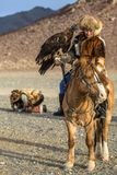 Kazakh Eagle Hunter Berkutchi with horse while hunting to the hare with a golden eagles on his arms. SAGSAY, MONGOLIA - SEP 28, 2017: Kazakh Eagle Hunter Stock Images