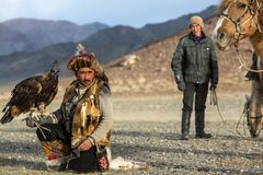 Kazakh Eagle Hunter Berkutchi with horse while hunting to the hare with a golden eagles on his arms. SAGSAY, MONGOLIA - SEP 28, 2017: Kazakh Eagle Hunter Stock Photo