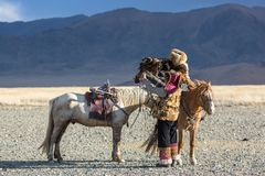 Kazakh Eagle Hunter Berkutchi with horse while hunting to the hare with a golden eagles on his arms. SAGSAY, MONGOLIA - SEP 28, 2017: Kazakh Eagle Hunter Royalty Free Stock Images