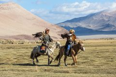 Kazakh Eagle Hunter Berkutchi with horse teaches his daughter to hunting to the hare with a golden eagles royalty free stock photos