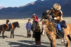 Kazakh Eagle Hunter Berkutchi with horse teaches his daughter to hunting to the hare with a golden eagles. SAGSAY, MONGOLIA - SEP 28, 2017: Kazakh Eagle Hunter Stock Photo