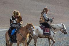 Kazakh Eagle Hunter Berkutchi with horse teaches his daughter to hunting to the hare with a golden eagles. SAGSAY, MONGOLIA - SEP 28, 2017: Kazakh Eagle Hunter Stock Images