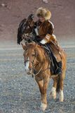 Young Kazakh Eagle Huntress Berkutchi woman with horse while hunting to the hare with a golden eagles. SAGSAY, MONGOLIA - SEP 28, 2017: Young Kazakh Eagle Royalty Free Stock Images
