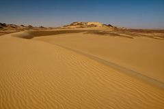 Sahara desert landscape with blue sky and dunes Royalty Free Stock Images