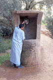 SAHARA DESERT, MOROCCO 20 OCTOBER 2013: Man in traditional cloth. Es drinking water from the well royalty free stock photos