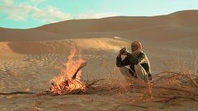 Sahara man near a fire. A man camping in the sahara desert stock video footage