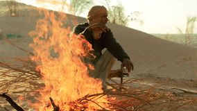 Sahara man near a fire. A man camping in the sahara desert stock video footage