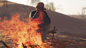 Sahara man near a fire. A man camping in the sahara desert stock video