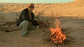 Sahara man near a fire. A man camping in the sahara desert stock footage