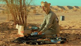 A sahara man washing dishes. A man camping in the sahara desert stock footage