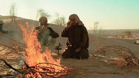Sahara men near a fire. Two men camping in the sahara desert stock video