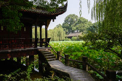 Sahded slabstone bridge to aged Chinese building in lotus lake Royalty Free Stock Images