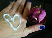 Sahneherz auf einer Handgesundheits- und -rosenblume lizenzfreie stockfotos