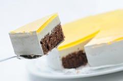 Sahnekuchen auf dem Metalllöffel, scharf auf weißer Platte, Kuchen mit gelber Gelatine, Konditorei, Fotografie für Shop, Geburtst Lizenzfreies Stockbild