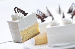 Sahnekuchen auf dem Metalllöffel, scharf auf weißer Platte, Kuchen mit roter Gelatine, Konditorei, Fotografie für Shop Lizenzfreie Stockfotos