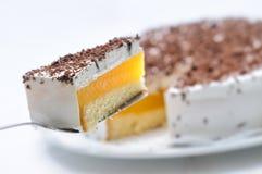 Sahnekuchen auf dem Metalllöffel, scharf auf weißer Platte, Kuchen mit roter Gelatine, Konditorei, Fotografie für Shop, Geburtsta Stockfotografie