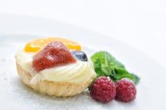 Sahnekuchen auf weißer Platte, Kuchen mit Erdbeeraprikosenhimbeeren und Blaubeere, tadellose Dekoration, Konditorei, Süßspeise Lizenzfreies Stockbild