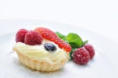 Sahnekuchen auf weißer Platte, Kuchen mit Erdbeerhimbeeren und Blaubeeren, tadellose Dekoration, Konditorei, Süßspeise Lizenzfreie Stockfotografie